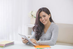 asian female student at home using tablet Stock Photo
