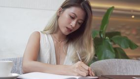 Asian female student learning english language. Writing in notebook stock video footage