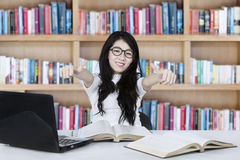 Asian female student with OK gesture. Image of Asian female student showing OK gesture while smiling at the camera and studying in the library Royalty Free Stock Image