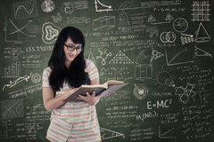 Asian female student reading book on chalkboard background Stock Photos