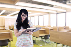 Asian female student reading book in classroom. Beautiful female student is reading book in classroom Royalty Free Stock Photo