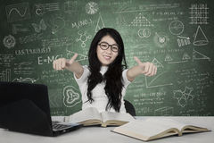 Asian female student showing thumbs up. Image of Asian female student showing thumbs up while studying in the class with doodles on the chalkboard Royalty Free Stock Images