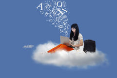 Asian female student sit on cloud with laptop and letters. Beautiful female student sitting on a cloud under blue sky with laptop and flying letters Royalty Free Stock Image