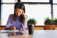 Asian female student sitting in cafe and writing on notebook Royalty Free Stock Image