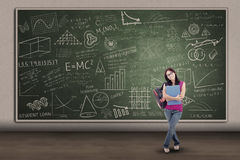 Asian female student standing at written board Royalty Free Stock Images