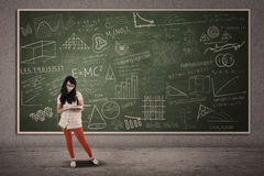 Asian female student standing on written board Royalty Free Stock Photography