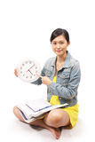Asian female student studying and holding clock Stock Photography