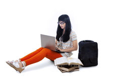 Asian female student typing on laptop - isolated Royalty Free Stock Image