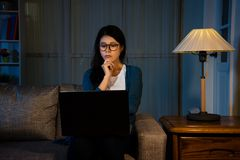 Asian female student watching the latest movie. Online all night sitting on the sofa enjoying film video story thinking with hand gesture at home in the living Royalty Free Stock Photography