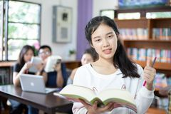Asian female students holding for selection Book in library stock images