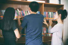 Asian female students holding for selection Book  in library. Asian female students holding selection Book in library Stock Photos