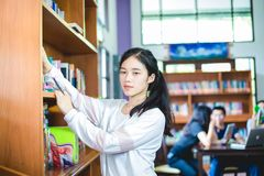 Asian female students holding for selection Book  in library Royalty Free Stock Photos