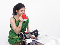 Asian female tailor drinking tea Stock Photo