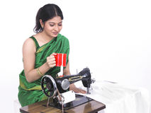 Asian female tailor drinking tea Royalty Free Stock Image