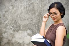 Asian female teacher. Portrait of pretty asian female teacher with eyeglasses holding literature on hands royalty free stock photos