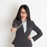 Asian female teacher holding a stick. Pointing at camera, standing on plain background royalty free stock images