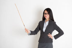Asian female teacher in serious expression. Asian female teacher angry and holding a stick, standing on plain background stock photography