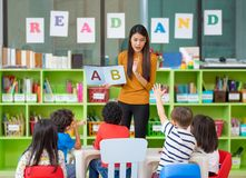 Asian female teacher teaching and asking mixed race kids hand up royalty free stock images