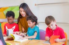 Asian female teacher teaching diversity kids reading book in classroom,Kindergarten pre school concept. Asian female teacher teaching diversity kids reading stock images