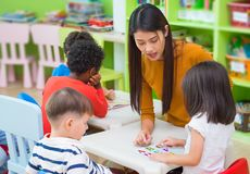 Asian female teacher teaching mixed race kids reading book in cl Royalty Free Stock Photos