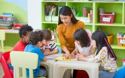 Asian female teacher teaching mixed race kids reading book in cl. Assroom,Kindergarten pre school concept Stock Photo