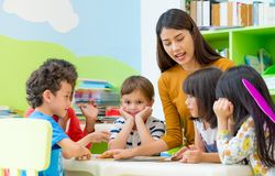 Asian female teacher teaching mixed race kids reading book in cl. Assroom,Kindergarten pre school concept Royalty Free Stock Photo