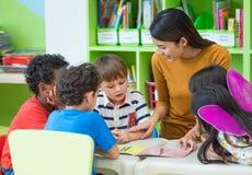 Asian female teacher teaching mixed race kids reading book in cl. Assroom,Kindergarten pre school concept Royalty Free Stock Photos