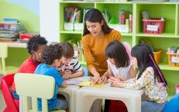 Asian Female Teacher Teaching Mixed Race Kids Reading Book In Cl Stock Photo