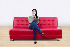 Asian female thinking on red sofa with laptop at h Stock Photos