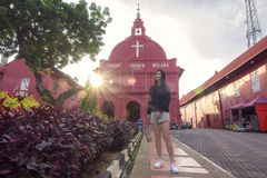 Asian female tourist enjoying the scenic view of Malacca town, with centuries old Christ church as background stock image