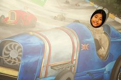 Asian female tourist scene. NEW FOREST ENGLAND -OCT 14 :  Asian female tourist visit national motor museum  and enjoy with photo backdrop represent british Royalty Free Stock Image