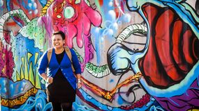Big smile in front of mural