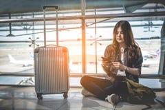 Asian female traveler using smart phone for checking flight time stock photo