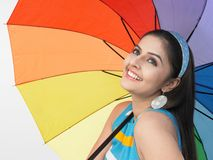Asian female with an umbrella. A pretty asian female with a rainbow umbrella Royalty Free Stock Photos