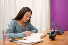 Asian female university student read book. Female university student in house read text book and write or take note, working on tabe with laptop, grass of water stock images