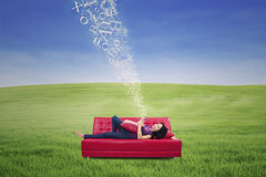 Asian female using touchpad on sofa with flying letters outdoor Royalty Free Stock Photos