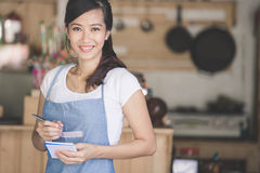 Asian female waiter in apron writing order. Happy attractive asian female waiter in apron writing order and looking at camera Royalty Free Stock Image