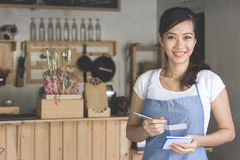 Asian female waiter in apron writing order. Happy attractive asian female waiter in apron writing order and looking at camera Royalty Free Stock Photos