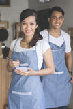 Asian female waiter in apron writing order. Happy attractive asian female waiter in apron writing order and looking at camera. her partner at the background Stock Photos