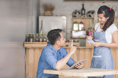 Asian female waiter in apron writing order. Happy attractive asian female waiter in apron writing order of a male customer Royalty Free Stock Photography