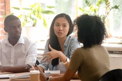 Asian female worker speaking telling opinion talking to african colleagues. At diverse group meeting sharing creative idea, chinese employee offering solution royalty free stock photo