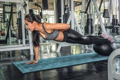 Female working out with push up in gym. Asian female working out with push up in gym stock images