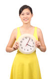 Asian female in yellow dress holding clock Stock Image