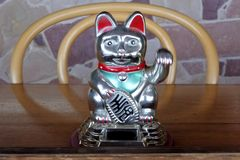 Asian figurine lucky charm talisman cat. On a wooden restaurant table stock image