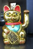 Asian figurine lucky charm talisman cat. On a wooden restaurant table stock photos