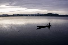 Asian fisherman boating across lake royalty free stock image