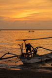 Asian Fisherman on his boat. Silhouette of an unknown asian fisherman preparing is primitive boat at sunset and getting ready for fishing.  Picture taken in Bali Royalty Free Stock Photo
