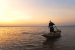Asian fisherman with his wooden boat Royalty Free Stock Photography