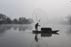 An Asian fisherman with traditional and ancient fishing net and boat works in morning fog Royalty Free Stock Photography