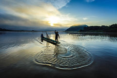 Asian fisherman on wooden boat casting a net for catching freshwater fish in nature river in the early morning before sunrise stock images